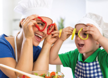 mother and son having fun preparing a meal and holding up bell pepper slices to their eye in a playful manner