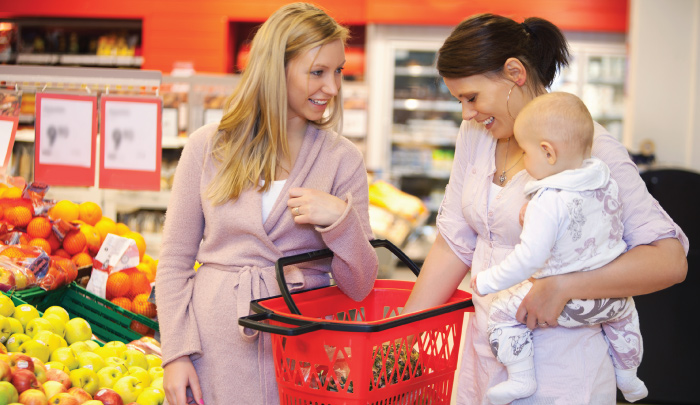 Two female friends shopping for groceries, both smiling, one holding the shopping basket, the other holding an infant child