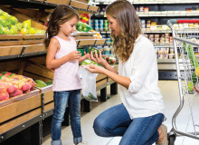 mother and daughter shopping for produce in grocery store