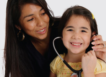 mother and daughter smiling and playing with stethoscope