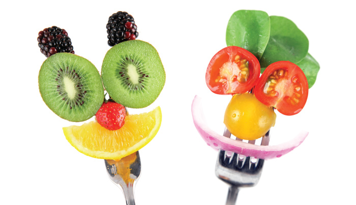 funny faces made from slices of various fruits and vegetables on held together on a pair of forks