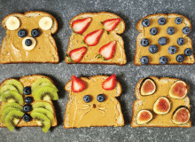 Six slices of peanut butter toast with various fruit toppings